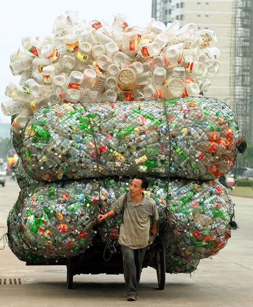 a man transports plastic bottles and containers for recycling.
