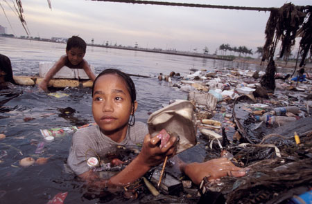 Children collecting floating waste for recycling, Manila Bay, Philippines.
