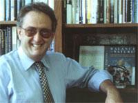 Stuart Pimm leans on a book case