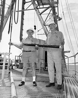 With Lamont cofounder Maurice Ewing (right) and sediment core, on deck of the deep-sea drilling ship Glomar Challenger, 1968