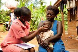 Community health worker examines child in Millennium Village of Bonsaaso, Ghana.