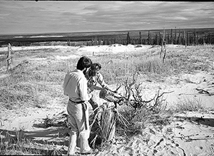 Jacoby takes a handsaw to an old log in northern Canada's Thelon River wilderness, circa 1984, as a colleague, Jobie Carlisle, looks on.