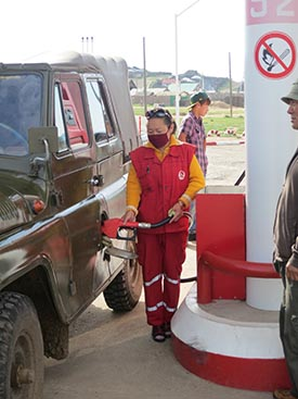 Countless human generations got their power from plants and animals; now, it's fossil fuels. A gas-station attendant in a small town fills up a jeep plying Mongolia's fast-spreading road network.