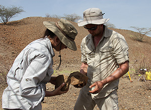 Sonia Harmand and Jason Lewis examine stone artifacts at the Lomekwi dig in Kenya.