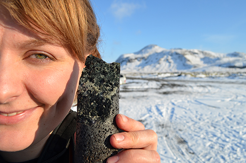 An experimental drill core held by coauthor Sandra Snaebjornsdottir is laced with solidified carbonate, apparently produced by a new process that turns carbon emissions to stone when pumped underground.
