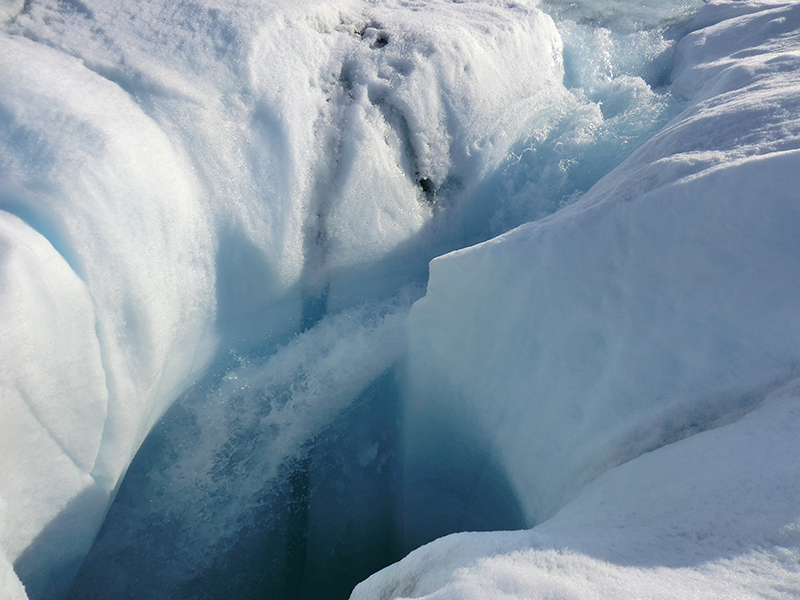 Melt water pours through a channel in Greenland's ice. (Marco Tedesco/Lamont-Doherty Earth Observatory)