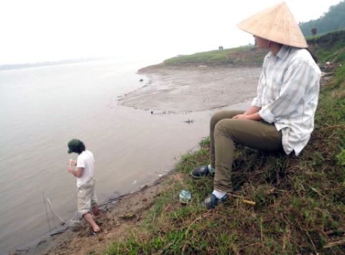 High concentrations of arsenic are making their way from the Red River into aquifers near Hanoi, Vietnam, a new study shows. Mason Stahl tests water at the river's edge where sediment is being deposited. Photo: Courtesy of Mason Stahl